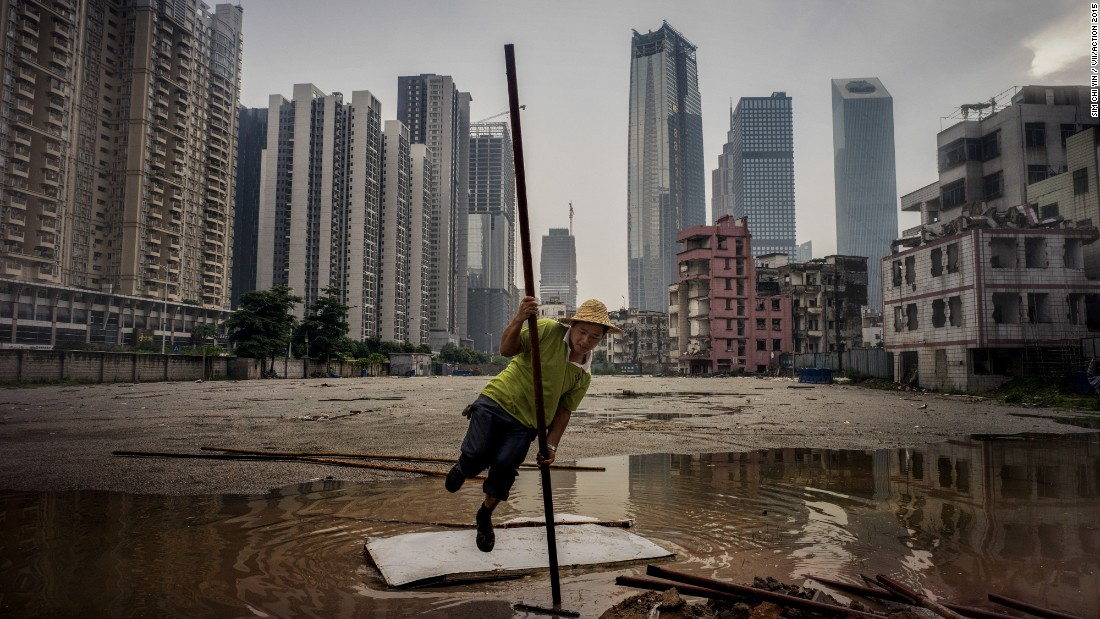 "China, Guangzhou, 2014 . A worker does an impromptu pole-vault across a puddle on the fringes of an urban village surrounded by new skyscrapers in Guangzhou, China's southern metropolis. All over China, people are being moved off the land and into apartment blocks, while rural land is turned into towns as China is swept by a government urbanization push. In 2012, a watershed was reached -- for the first time, there are more Chinese living in urban areas than rural ones.<br />Chi Yin is a fourth-generation overseas Chinese, born and raised in Singapore. She was named as the British Photographic Society's 'One to Watch' in 2014.<br /><br />Chi Yin: ""This unique part of Guangzhou illustrates the massive urbanization that's going on around China, but at the same time the uneven distribution of income and wealth. Five minutes walk from this is the US embassy is where a lot of expats hang out, a lot of posh hotels have opened up. Yet inside this urban village there are half-demolished, rat-infested buildings that are mostly lived in by migrant workers, who have come from all over China to build those skyscrapers."""