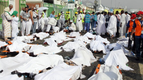 People stand near the bodies of victims at the site of the stampede.