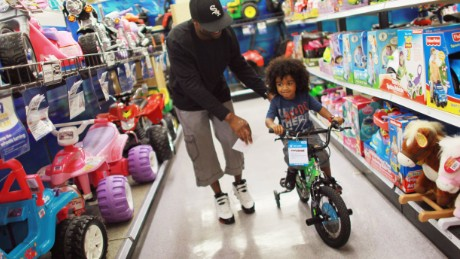 "MIAMI - SEPTEMBER 28:  Devin Mingot rides a bike as his father Wayne Mingot pushes him as he shops at the Toys""R""Us store on September 28, 2010 in Miami, Florida. Toys""R""Us announced today it will hire about 45,000 employees to help with the holiday season, a larger number than in previous holiday seasons.  (Photo by Joe Raedle/Getty Images)"