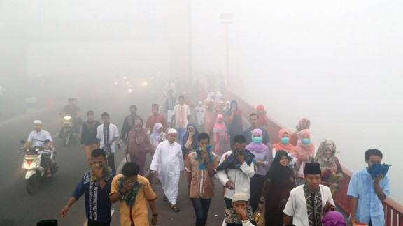 """Indonesians cover their mouths and noses from the pollution as they travel to attend a morning prayer celebrating Eid al-Adha, or the """"Festival of Sacrifice,"""" in Palembang, South Sumatra on September 24."""