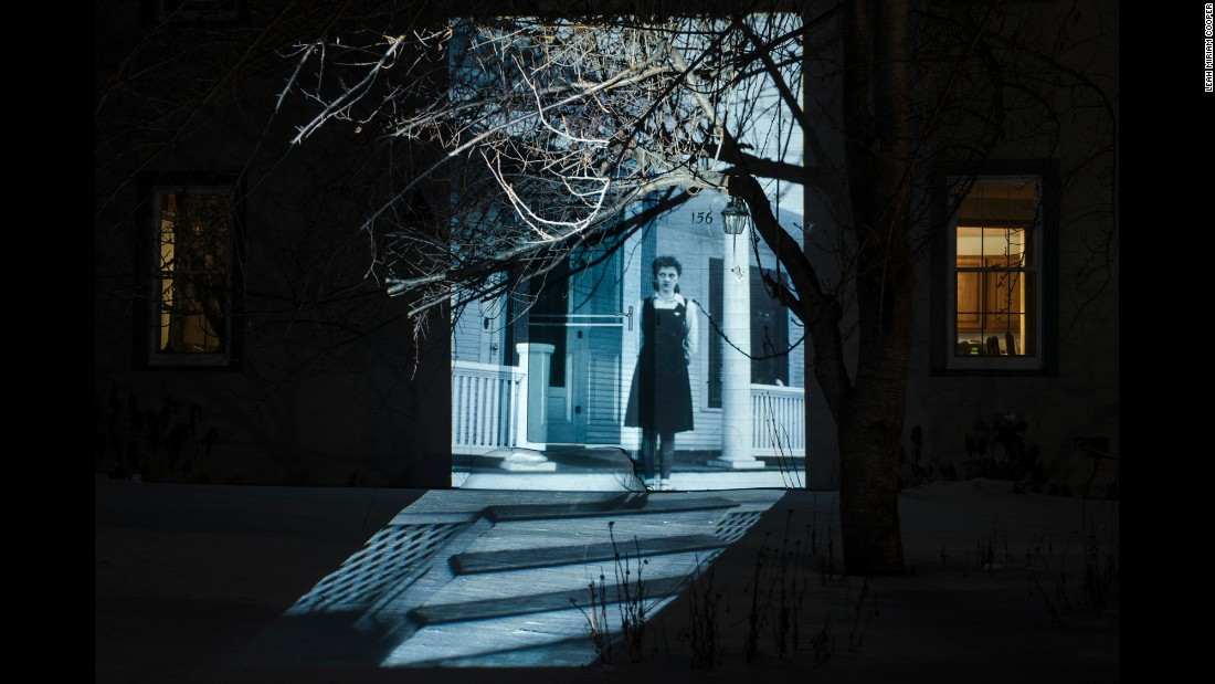 Leah Miriam Cooper collected old family photographs and projected them onto her home. She said the project helped her feel closer to the relatives she never really knew. Seen here is Cooper's paternal grandmother, Hannah, standing in front of her Nebraska home in 1943. The image was projected onto Cooper's Rhode Island home in February.