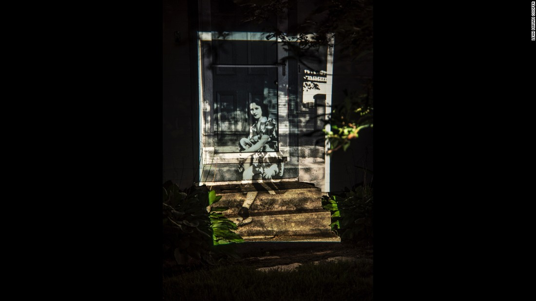 An image of an unknown family member, sitting on a stoop in 1944, is projected onto Cooper's home.