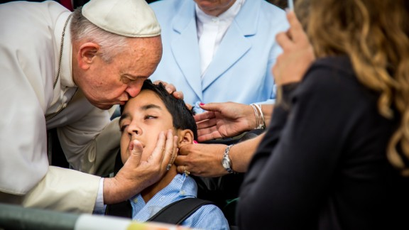 Pope Francis kisses and blesses Michael Keating, 10, of Elverson, Pennsylvania, after arriving in Philadelphia on September 26.  Keating has cerebral palsy and is the son of Chuck Keating, director of the Bishop Shanahan High School band, which performed at Pope Francis' airport arrival.