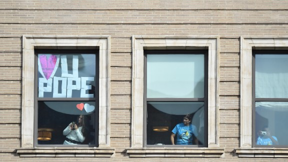 Residents in decorated apartment windows await the arrival of Pope Francis near Independence Mall on September 26.