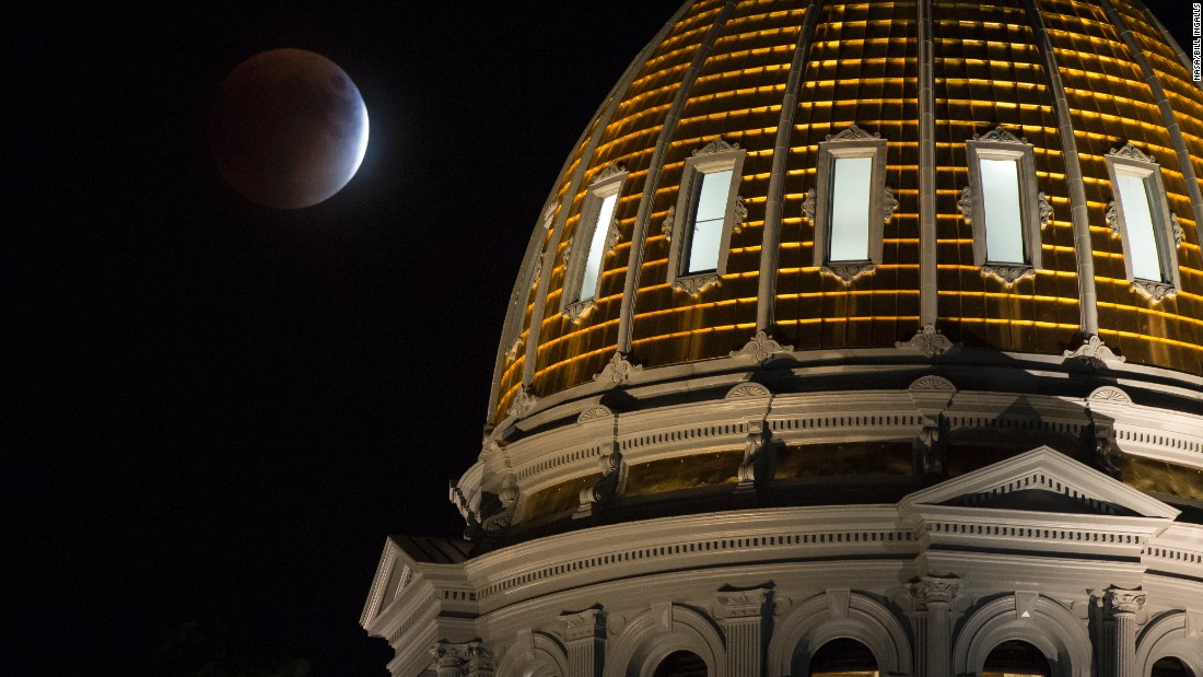 The supermoon is shown during the eclipse next to the Colorado State Capitol building in Denver.