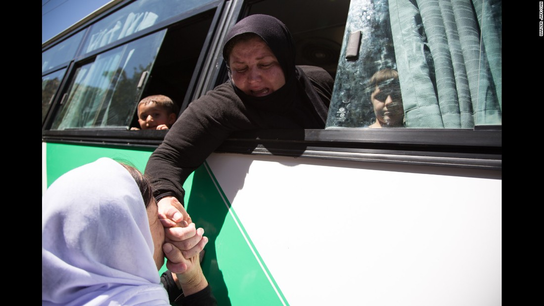 A Yazidi woman kisses the hand of a relative before a bus takes women and children who were captives of ISIS to an airport in the Kurdish region of Iraq. From there, they will fly to Germany, where the German government is resettling up to 1,000 former captives of ISIS, giving them housing and psychological treatment.