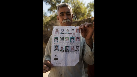 Jamil Jato shows photos of family members who were murdered by ISIS.