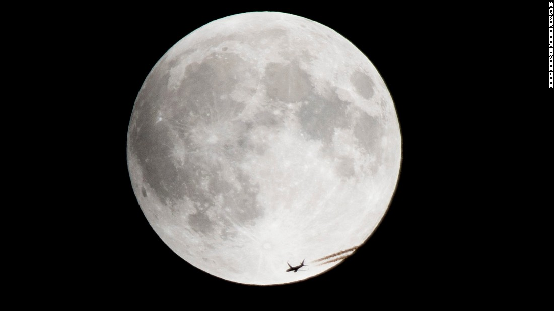 A plane passes by the rising supermoon in Montreal.