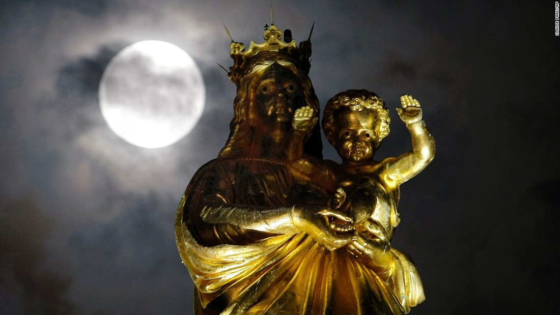 The supermoon passes by a statue of the Virgin Mary and the Child at Notre Dame de La Garde basilica in Marseille, France.