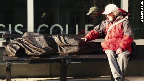 A statue, created by Timothy Schmalz, depicts Jesus as a homeless person, sleeping on a park bench.