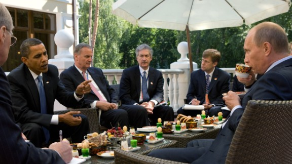 Obama, who had become U.S. President six months earlier, enjoys tea with then-Prime Minister Vladimir Putin and members of the American delegation at Putin