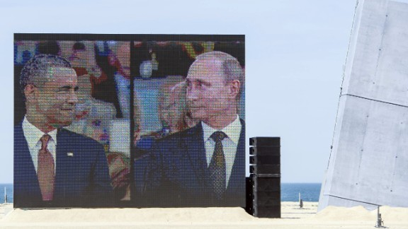 "Obama and Putin share a comical and awkward moment on a large split-screen during an international ceremony on the stretch code-named Sword Beach, in Ouistreham, France, to commemorate the Allied invasion of Normandy on June 6, 2014. Obama and Putin had an informal 15-minute chat during lunch at the ceremony that marked the 70th anniversary of the D-day landings. ""It"