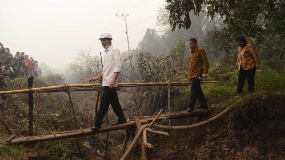 Indonesia's President Joko Widodo, in white, inspects a firefighting operation on burning peatland in Borneo.