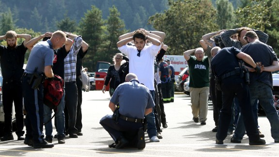 Police search students outside Umpqua Community College after a deadly shooting at the school in Roseburg, Oregon, in October 2015. Nine people were killed and at least nine were injured, police said. The gunman, Chris Harper-Mercer, committed suicide after exchanging gunfire with officers, a sheriff said.