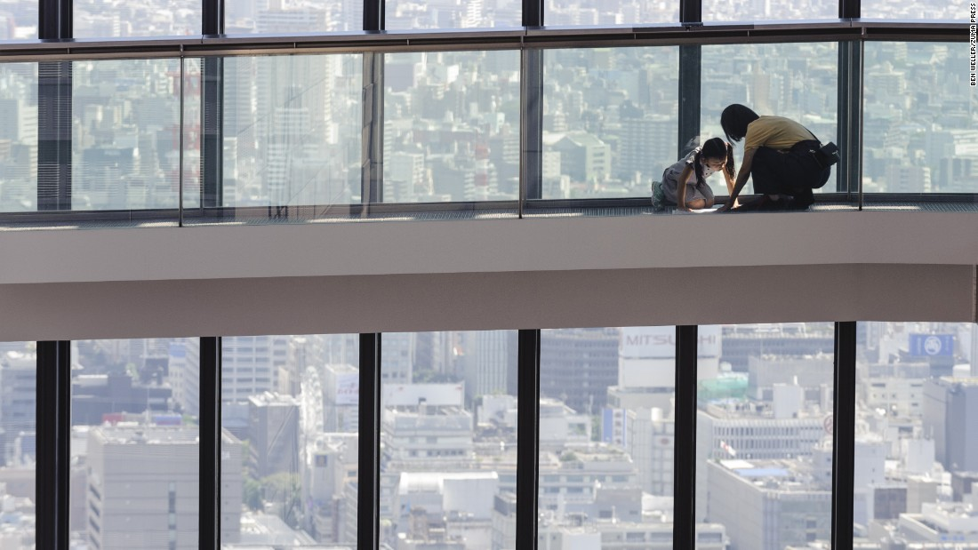 A woman and child examine a map on the Sky Promenade at Midland Square, a skyscraper in Nagoya, Japan, on Monday, September 28.