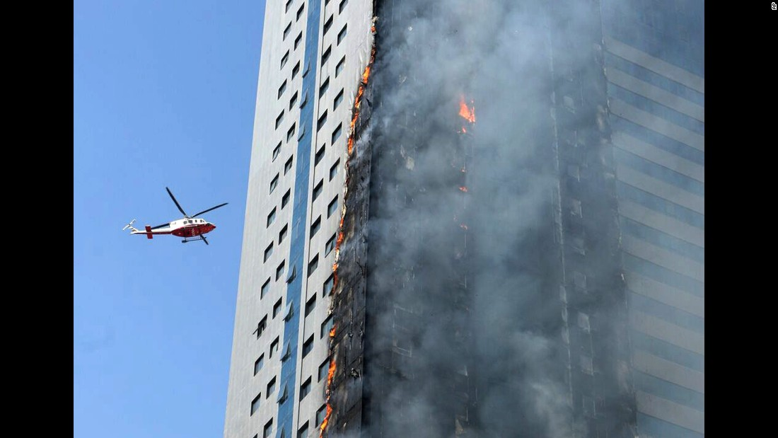 A helicopter flies near a skyscraper that caught fire in Sharjah, United Arab Emirates, on Thursday, October 1. It was not immediately clear whether there were any casualties.