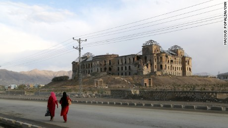 Two women walk down the road in front of the ruins of Darul Aman Palace in Kabul, Afghanistan.