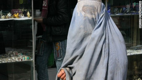 Woman wearing a burqa begs on a street in central Kabul, Afghanistan.