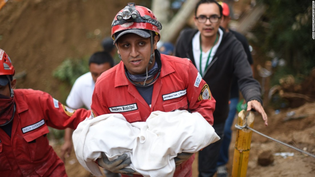 A rescuer carries the body of a child recovered from the mud and debris on October 2.
