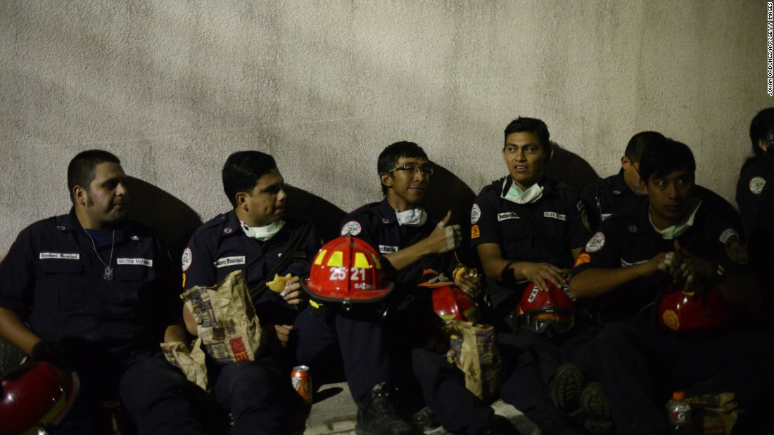 Municipal firefighters rest during rescue operations on October 2.