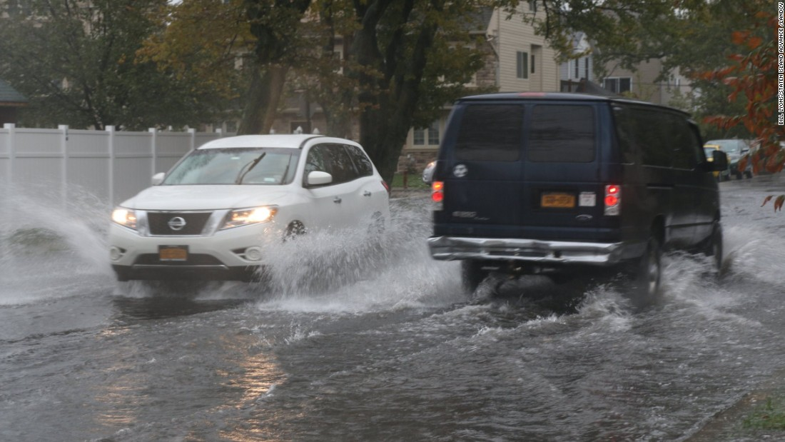Cars negotiate flooded streets on October 2 in Midland Beach on Staten Island, New York.