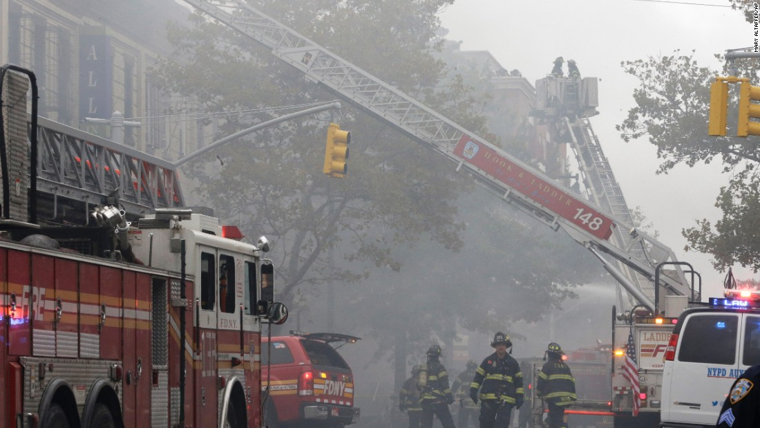 "Fire crews work the scene at the three-story building. Gov. Andrew Cuomo called for a state investigation into the incident, calling the recent trend of explosions ""disturbing."""