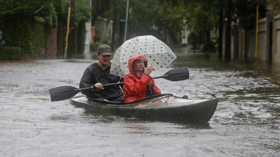 Paul Banker paddles a kayak as his wife, Wink Banker, takes photos on a flooded street in Charleston, South Carolina, on October 3.