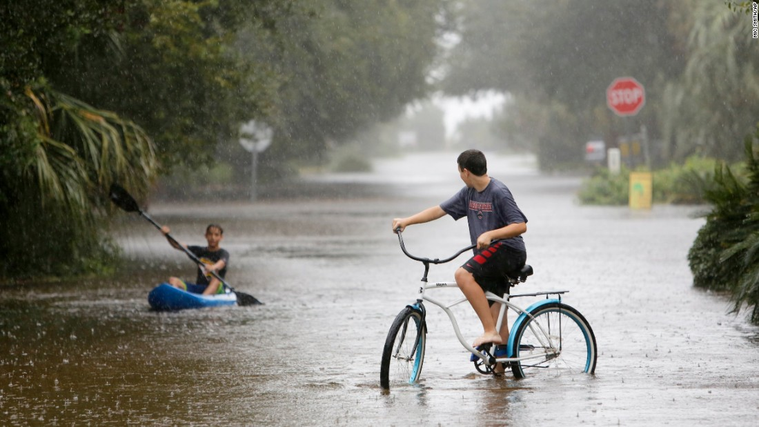Will Cunningham, 14, rides his bike down Station 29 on Sullivan's Island, South Carolina, ahead of his paddling  friend Patrick Kelly, 14, on October 3.