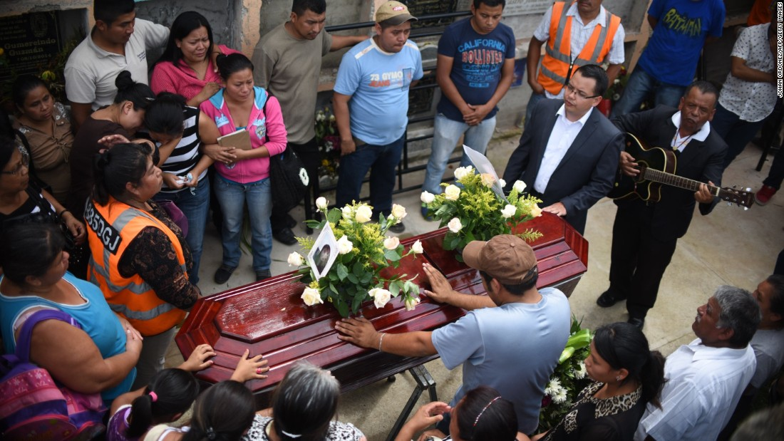 Relatives attend the burial of landslide victim Pamela Perez, 17, at a cemetery in Santa Catarina Pinula on October 3.