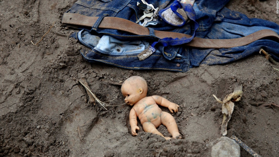 A doll and clothing lie in the mud as rescue workers continue to search the site of a mudslide on October 3.