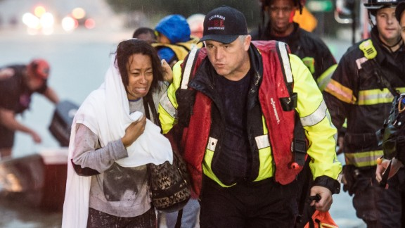 Charlene Stennis is escorted to safety after her son was rescued from a stranded vehicle during the heavy rains on October 4 in Columbia, South Carolina.