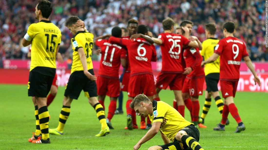 Bayern players celebrate their fifth goal against a dejected Borussia Dortmund team.