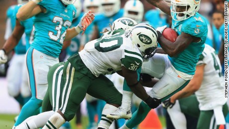 Darrin Walls of the Jets tackles Jarvis Landry of the Dolphins during the game at Wembley.