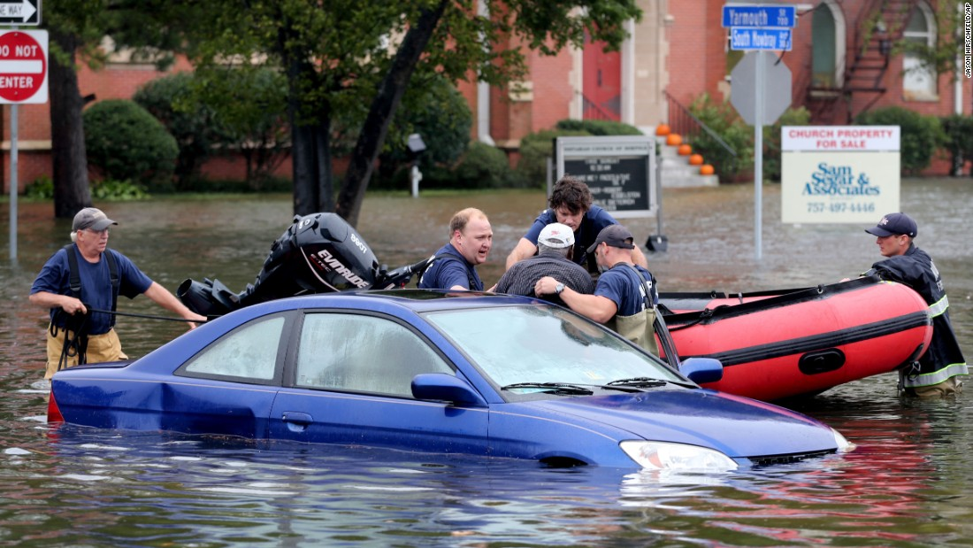 Members of Norfolk Fire-Rescue pull a man from his car in Norfolk, Virginia, on Sunday, October 4.