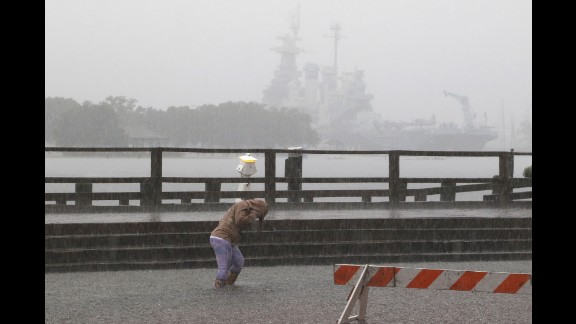 A person walks through the flooded Market and Water streets in downtown Wilmington, North Carolina, on October 4.