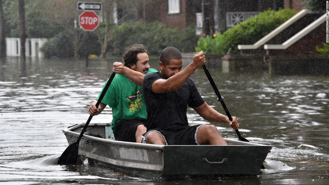 Two men row a boat on a flooded street in downtown Charleston, South Carolina, on October 4.