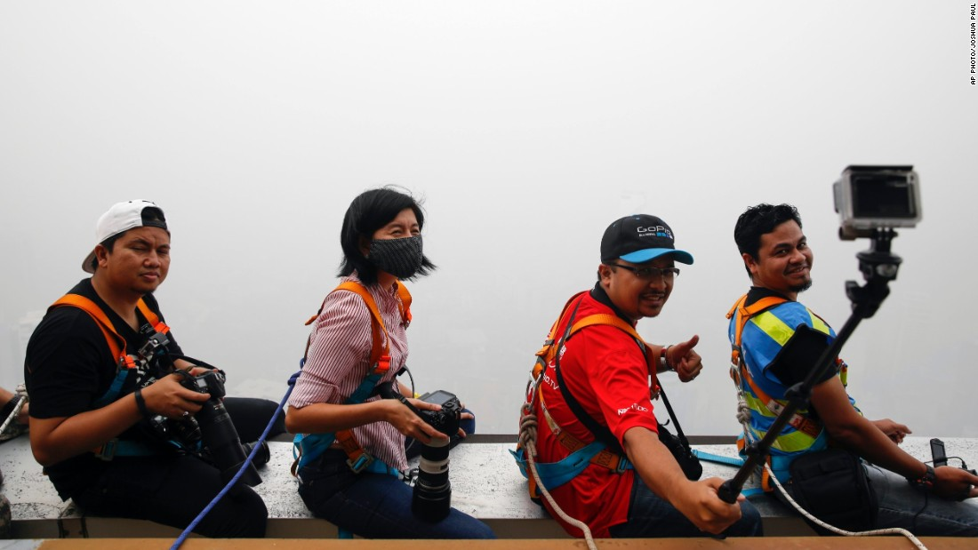 What was the subject of the selfie -- an aerial view of the capital, or the haze that is completely obscuring the view? Men and women snap a picture on top of the Kuala Lumpur Tower during the KL Tower International Jump on October 3.