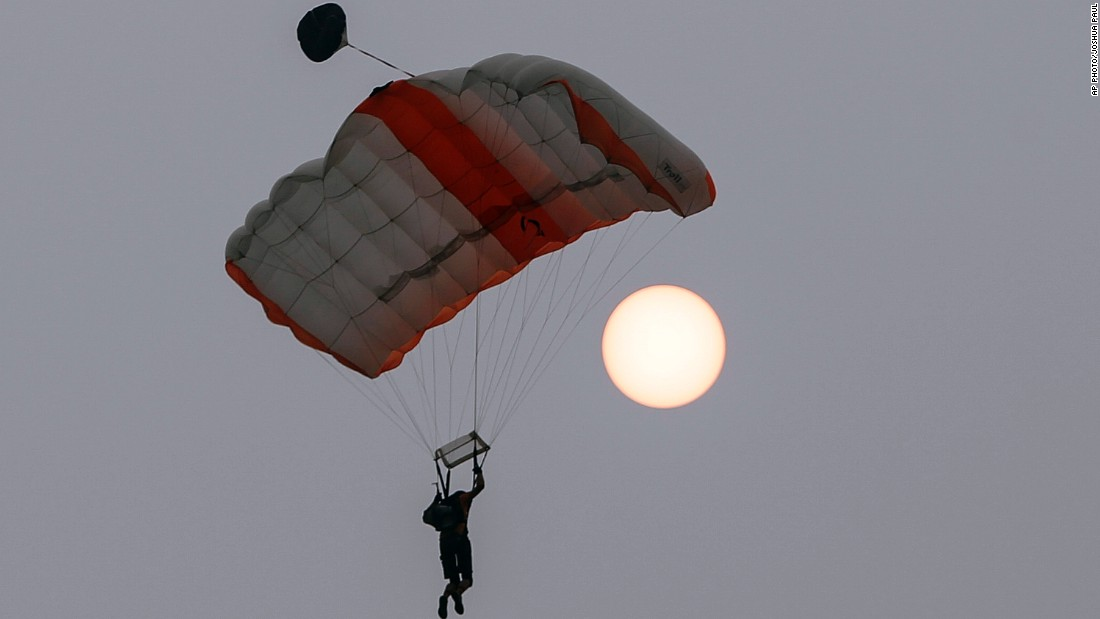 A BASE jumper parachutes past a red sun as haze continues to choke Kuala Lumpur on October 3.