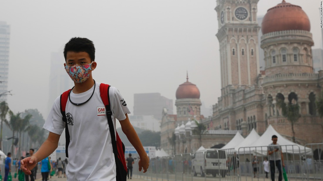 A man shields himself with a face mask from the smog enveloping Kuala Lumpur as he walks past the Sultan Abdul Samad Building on October 4.