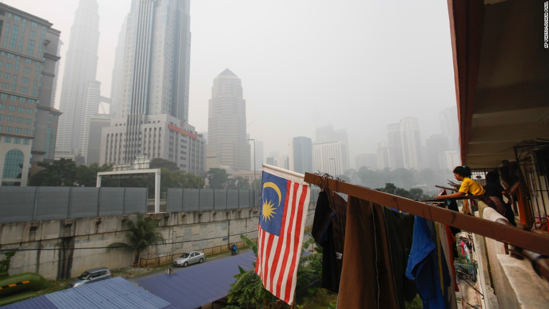A woman hangs her laundry amongst the haze on October 4 in Kuala Lumpur.