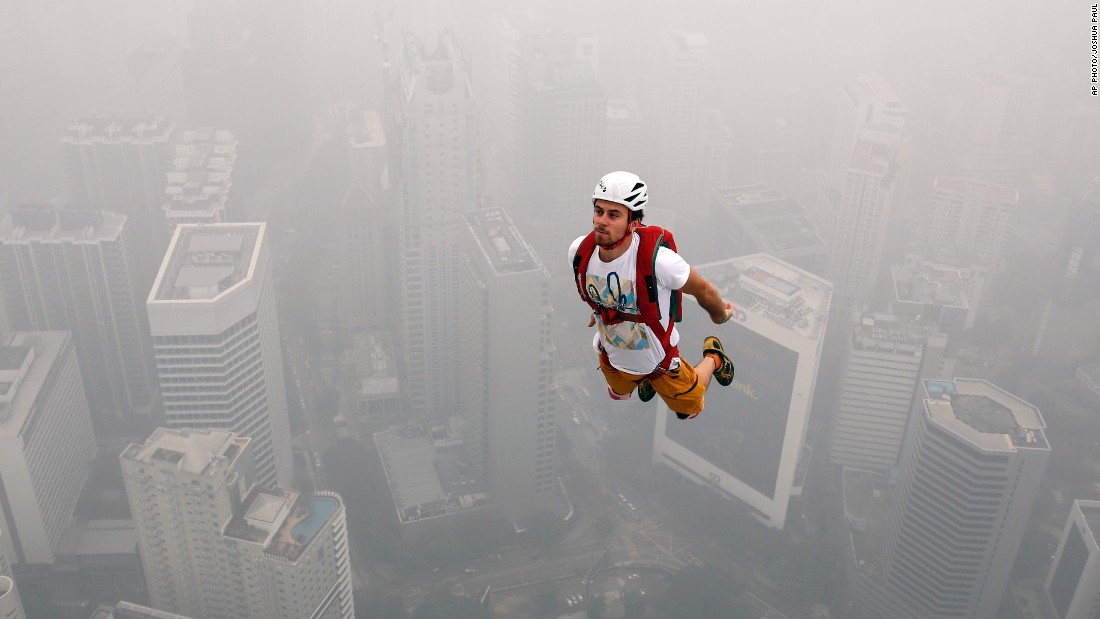 A BASE jumper dives into the haze from the Kuala Lumpur Tower during the KL Tower International Jump, held annually in the Malaysian capital, on October 3, 2015.