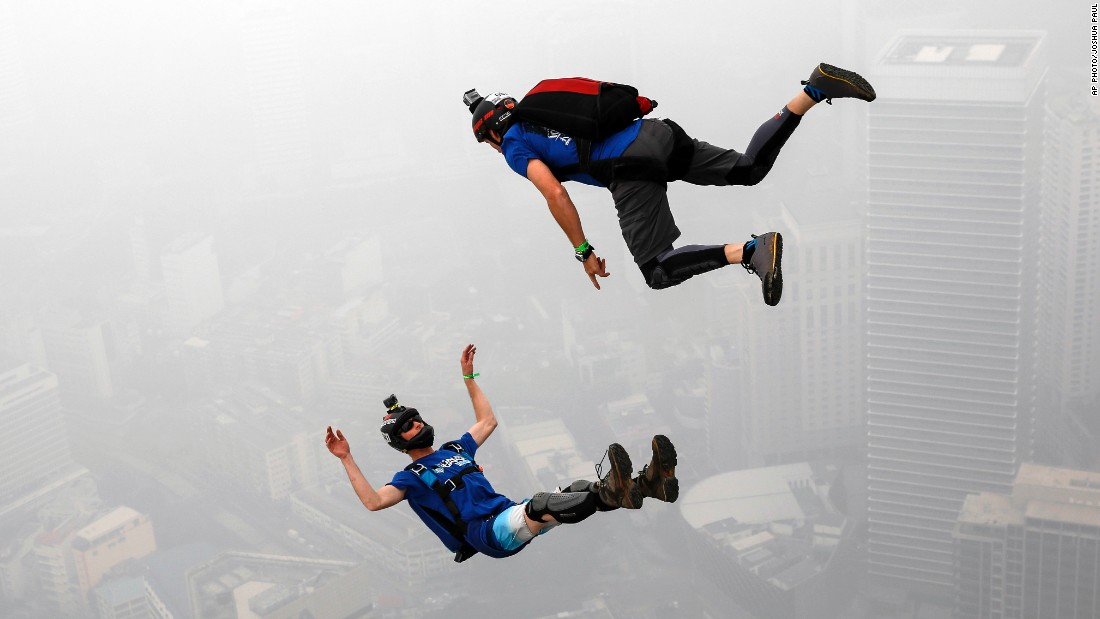 Undeterred by the haze that canceled a marathon, Australian BASE jumpers dive in tandem from the Kuala Lumpur Tower during the KL Tower International Jump on October 3.