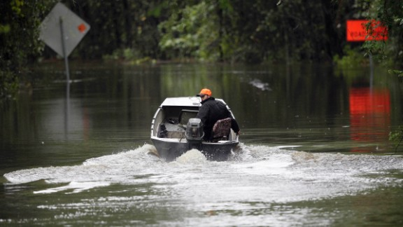 Hunter Baker drives his boat down a flooded East Black Creek Road to his home following heavy rains in Florence on October 5.