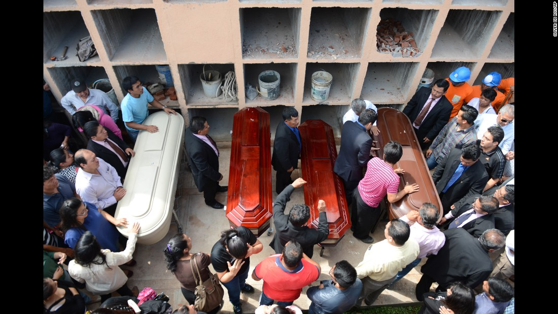 People in Santa Catarina Pinula surround the coffins of four landslide victims on Sunday, October 4.