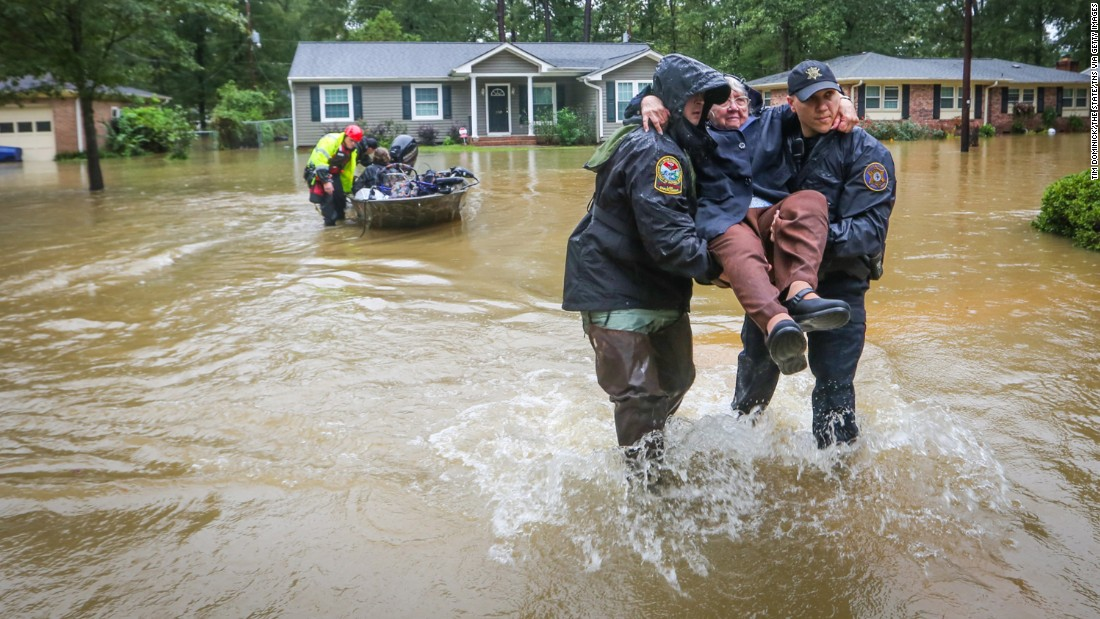 Police officers carry a woman to dry land after she was rescued from her home in the St. Andrews area of Columbia, South Carolina, on October 5.