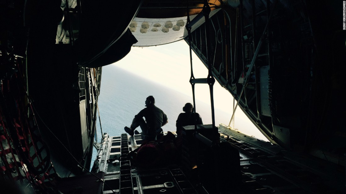 "The plane makes a sharp bank to ""orbit,"" or fly back over, a piece of debris that the crew wants to check. On the second pass, the cockpit crew gives it another look, as will the crewmember operating the onboard camera. Here, Petty Officers 3rd Class Chris LaBelle, left, and Mark Strock sit on the edge of the cargo door in hopes of getting a better perspective on the debris."