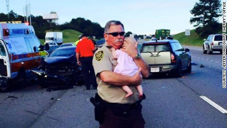 Deputy Ric Lindley holds a baby after a traffic accident near Leeds, Alabama, on Monday morning.