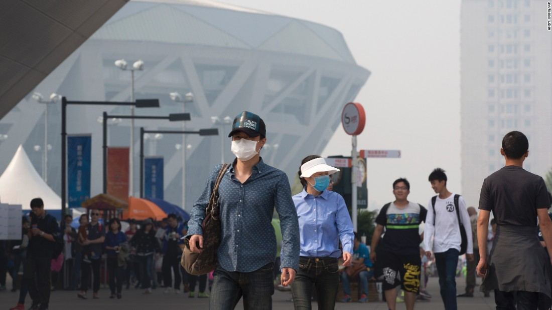 Tennis fans protecting themselves from pollutants walk past the National Tennis Stadium during the China Open tennis tournament in haze-hit Beijing on October 5.