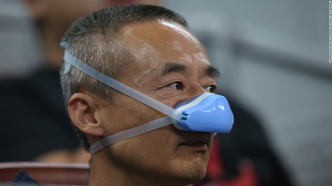 A man shields his nose from the smog during the match between Belinda Bencic of Switzerland and Madison Brengle of the United States at the National Tennis Stadium on October 5, 2015.