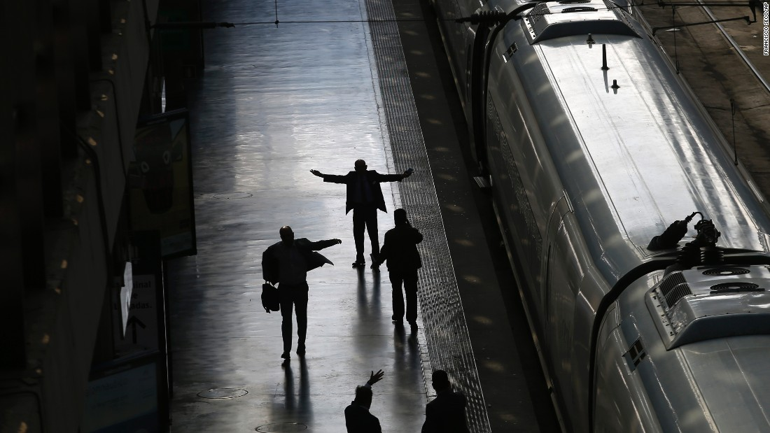 Railway staff supervise the departure of a Barcelona bound high-speed train at a station in Madrid on Thursday, October 8. High-speed train service throughout the northeastern region of Catalonia was suspended for hours on Thursday after thieves stole fiber-optic cable alongside the tracks that officials said was critical for maintaining train safety.